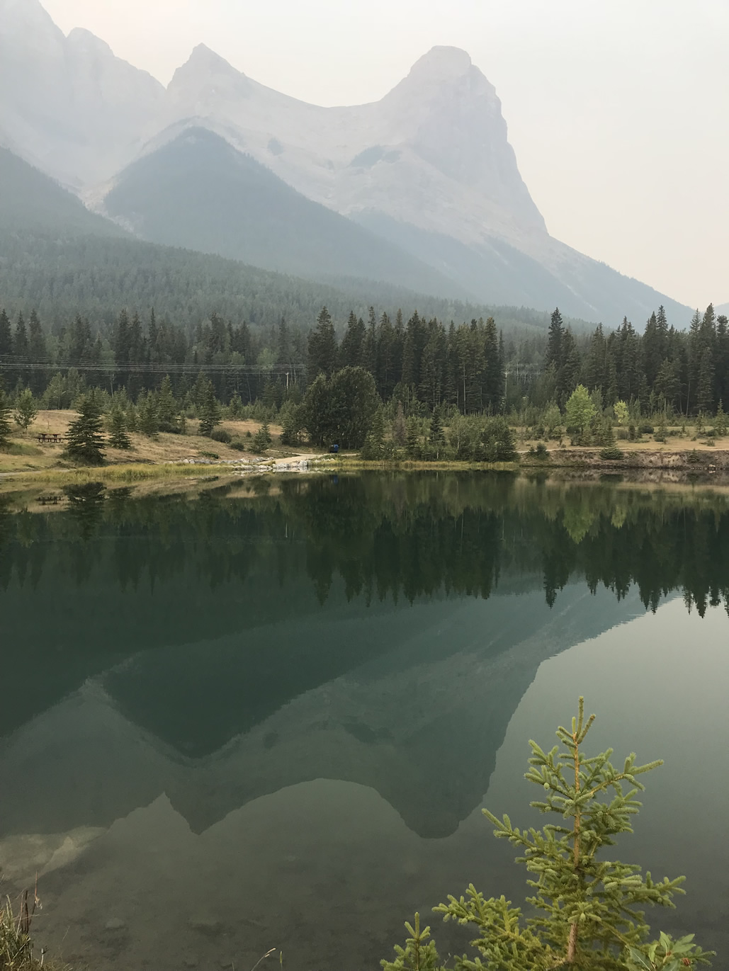 Hazy reflection at Canmore's Quarry pond (below Ha Ling Peak)